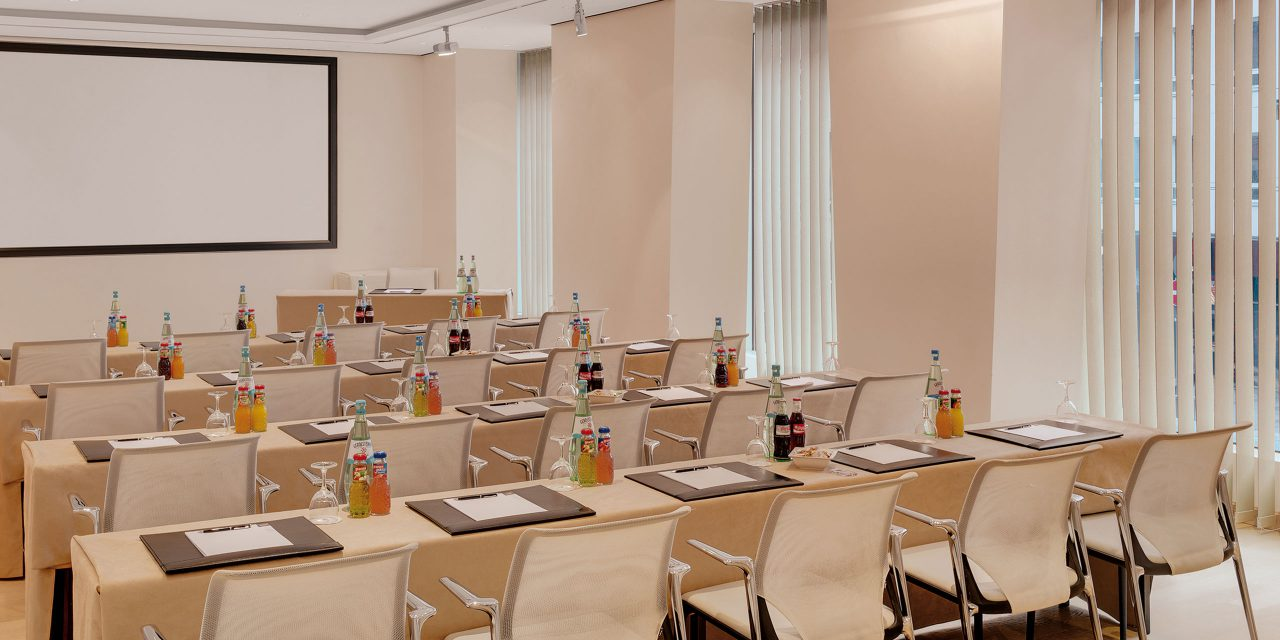 Seminar room number 5 in the Excelsior with tables and chairs in canvas direction, large windows and drinks as well as notes for the seminar participants of the conference hotel in Munich.