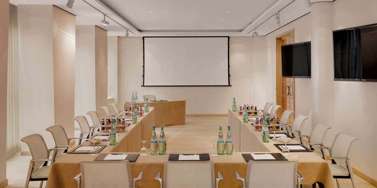 Seminar room in the conference hotel Excelsior in Munich with u-shaped and set tables as well as a large screen and a speaker's table in front.