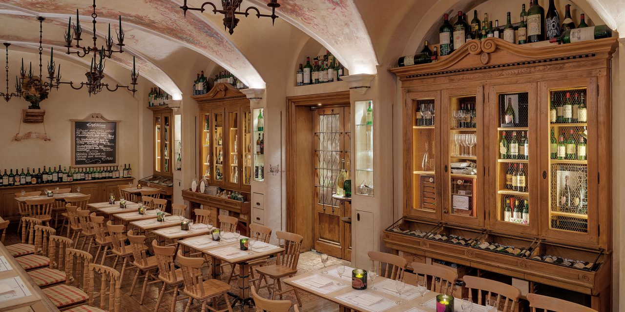 Rustic Geisel Vinothek in Munich with large wooden shelves with wine and many seats.
