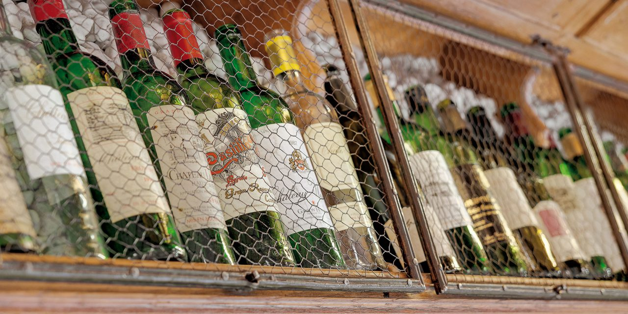 Various wine bottles on the shelf with lattice door in the Geisel Vinothek in Munich.