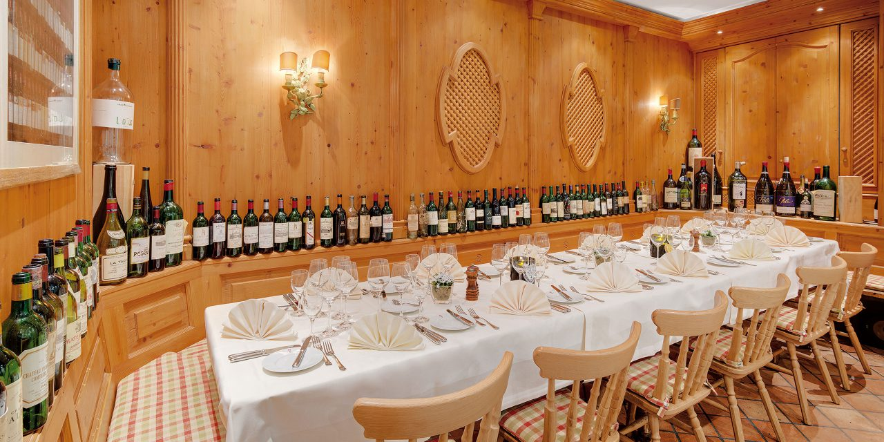 Large covered table in the show kitchen of the Hotel Excelsior in Munich with rustic wooden walls and numerous wine bottles on the backrest.