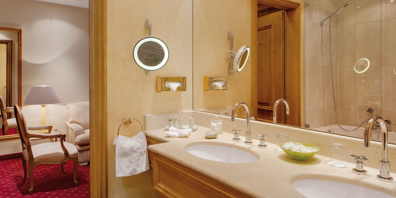 The bright bathroom has a warm atmosphare by reason of modern sink in cream colours and elegant details in a double room classic in the Hotel Excelsior by Geisel in Munich.