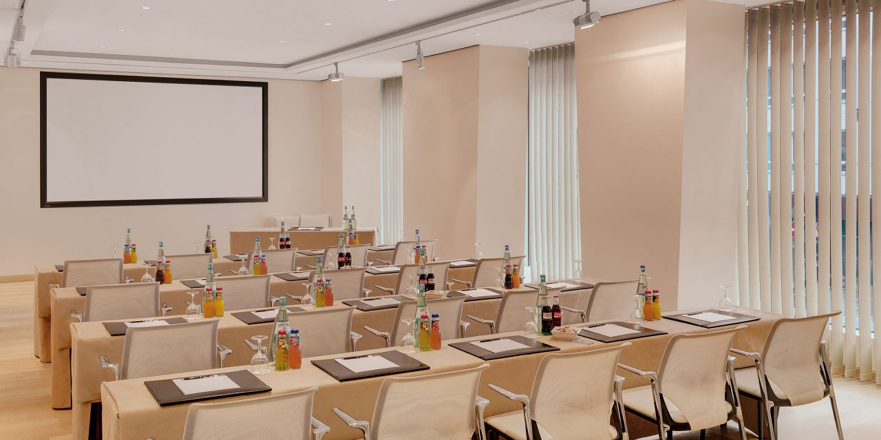Room 5 of the Excelsior conference hotel in Munich with a bright window front, large screen and tables and chairs facing the front.