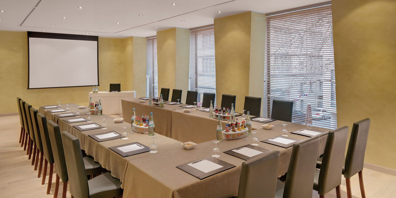 "Conference room ""Room Two"" in the Excelsior conference hotel in Munich with u-shaped seating and large screen."