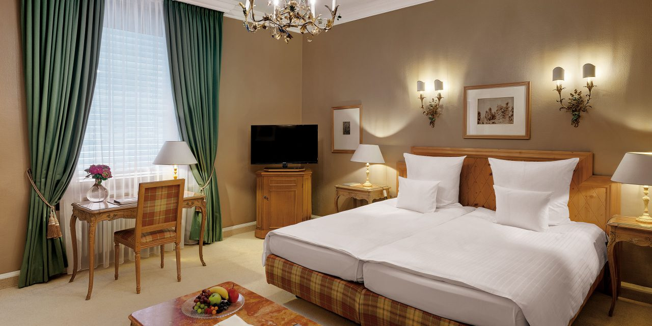 Room 2 in the Hotel Excelsior in Bavarian style with large bed, wooden furniture and large window with long curtains.