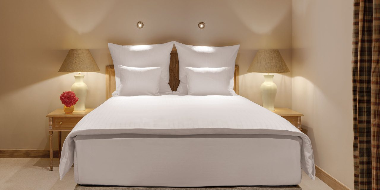 Large bed with bedside tables and table lamps in the Excelsior Hotel in the centre of Munich.
