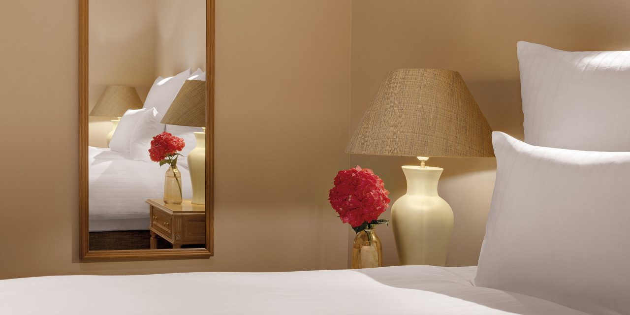 Detailed view of room 4 in the Hotel Excelsior in the center of Munich over the bed on a wooden mirror and red flower on the bedside table.