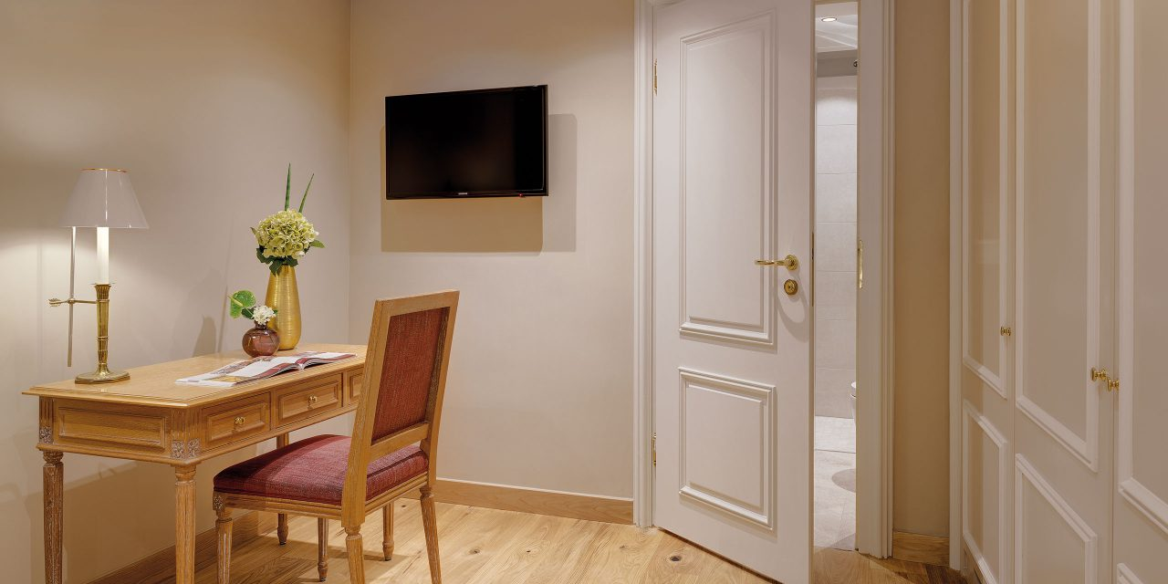 Sitting area in the hotel room of the Hotel Excelsior in Munich city centre with TV and desk including reading lamp and half-opened door to the bright bathroom.