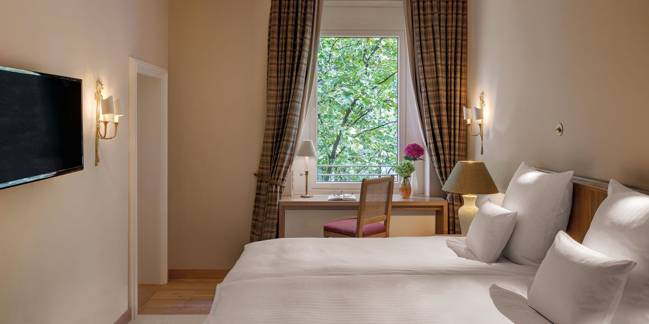 Hotel room in the Hotel Excelsior in downtown Munich with a large bed, TV, desk and a window view of a tree.