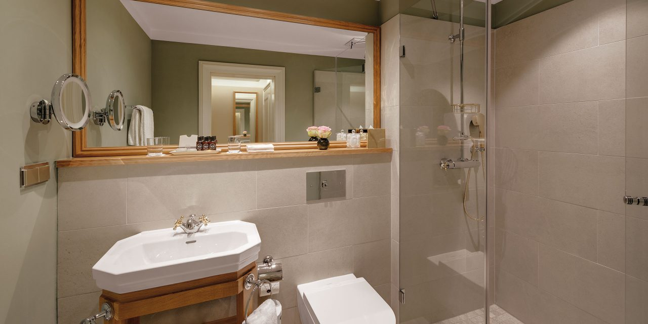 Elevated bathroom in a double room of the Hotel Excelsior inclusive with wood framed mirror and large shower.