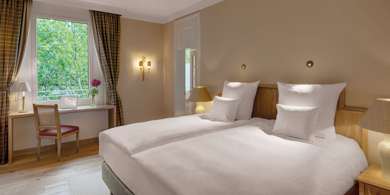 Room 13 in the Hotel Excelsior in the centre of Munich with large double bed, desk, chair and view into the greenery.