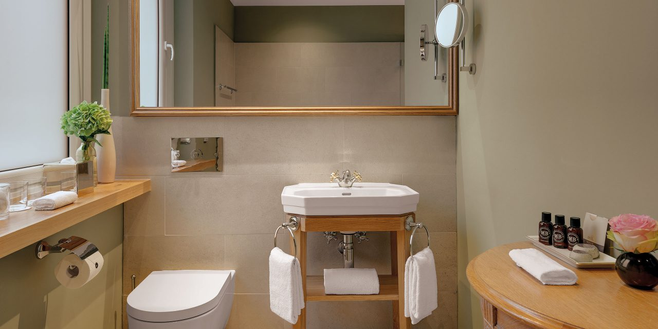 Luxurious bathroom with wide mirror, wooden elements, flowers and care products in Hotel Excelsior.