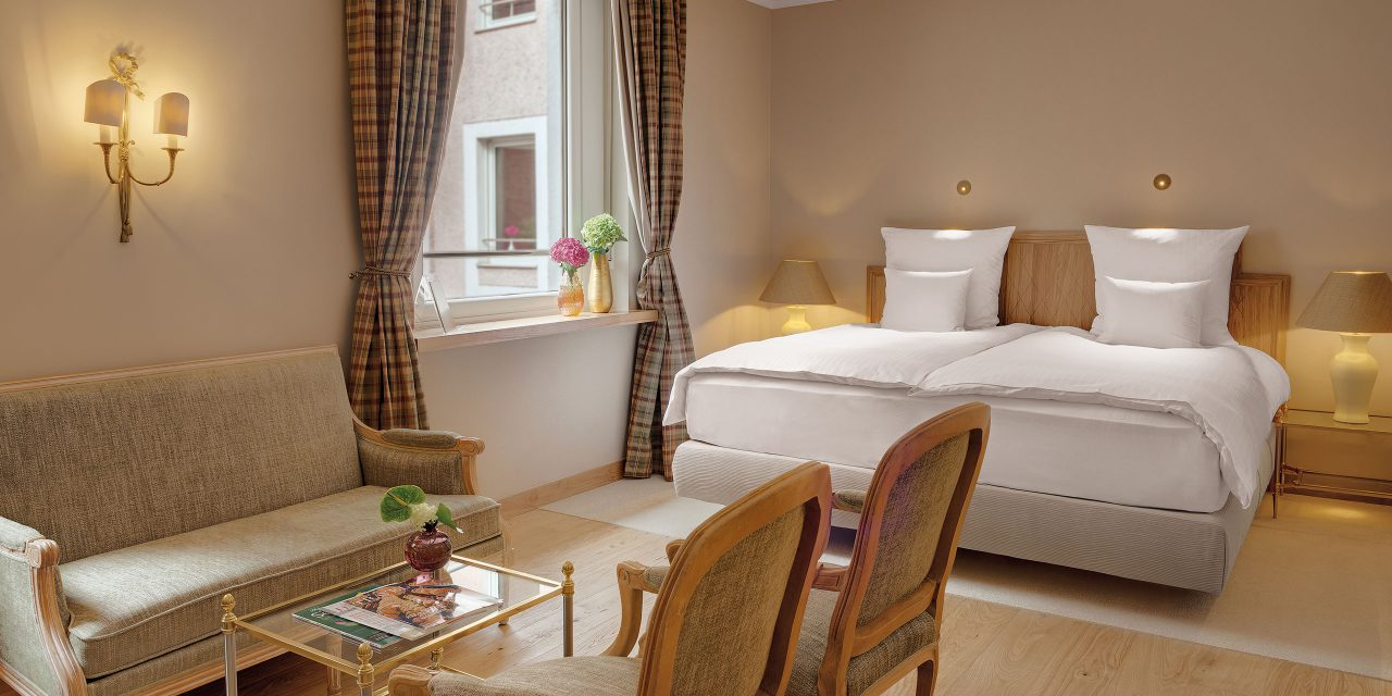 Bright room with checkered curtains, large bed and sitting area with couch and chairs in the double room Deluxe of the Hotel Excelsior in Munich.