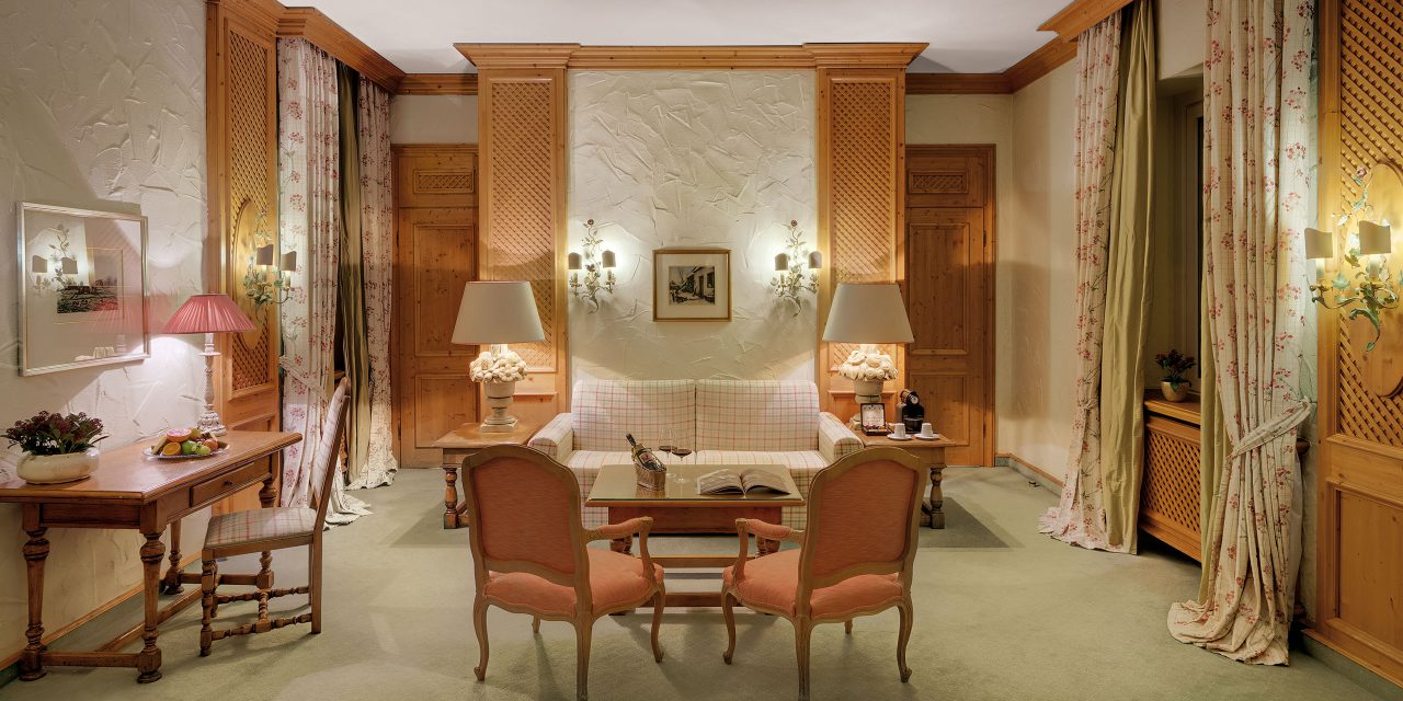 Bavarian Junior Suite in the Hotel Excelsior in Munich city centre with flowered curtains, cosy sitting area, fresh fruit platter and desk.