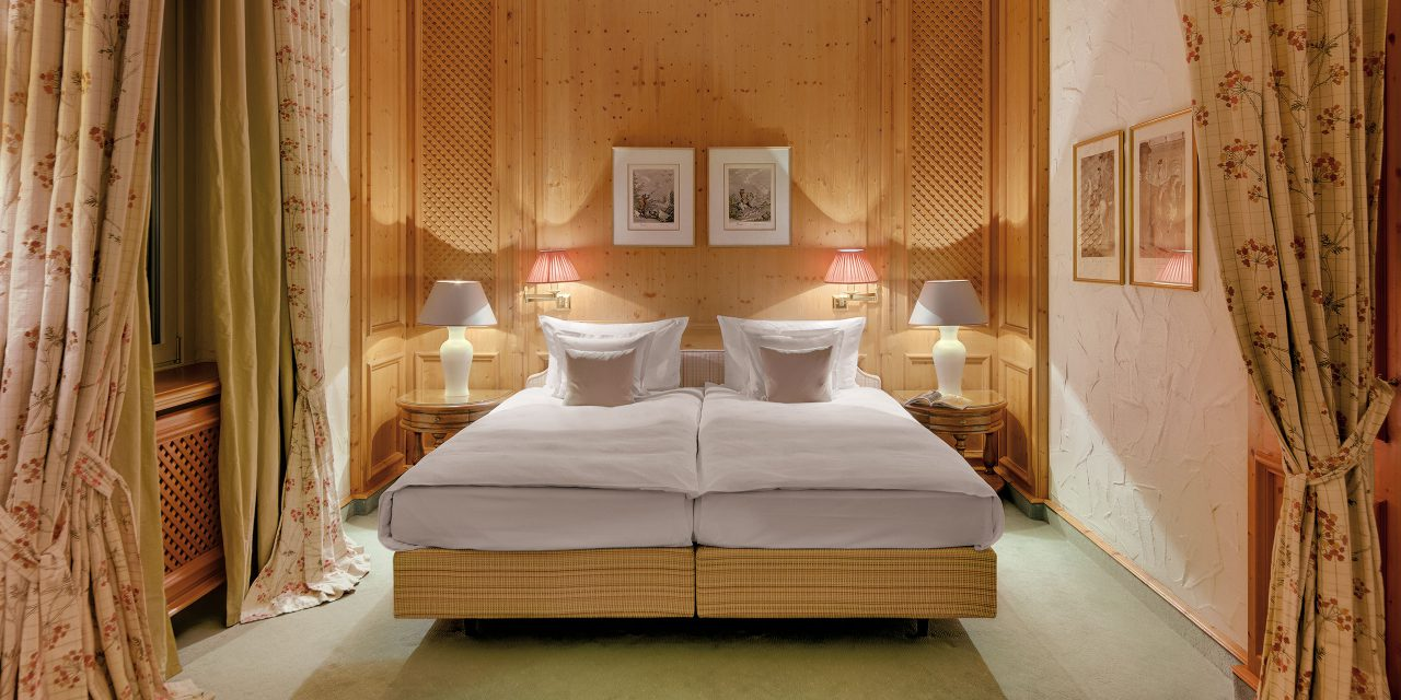 Bavarian furnished hotel room with wood clad wall, large bed, atmospheric lamps and long flowered curtains.