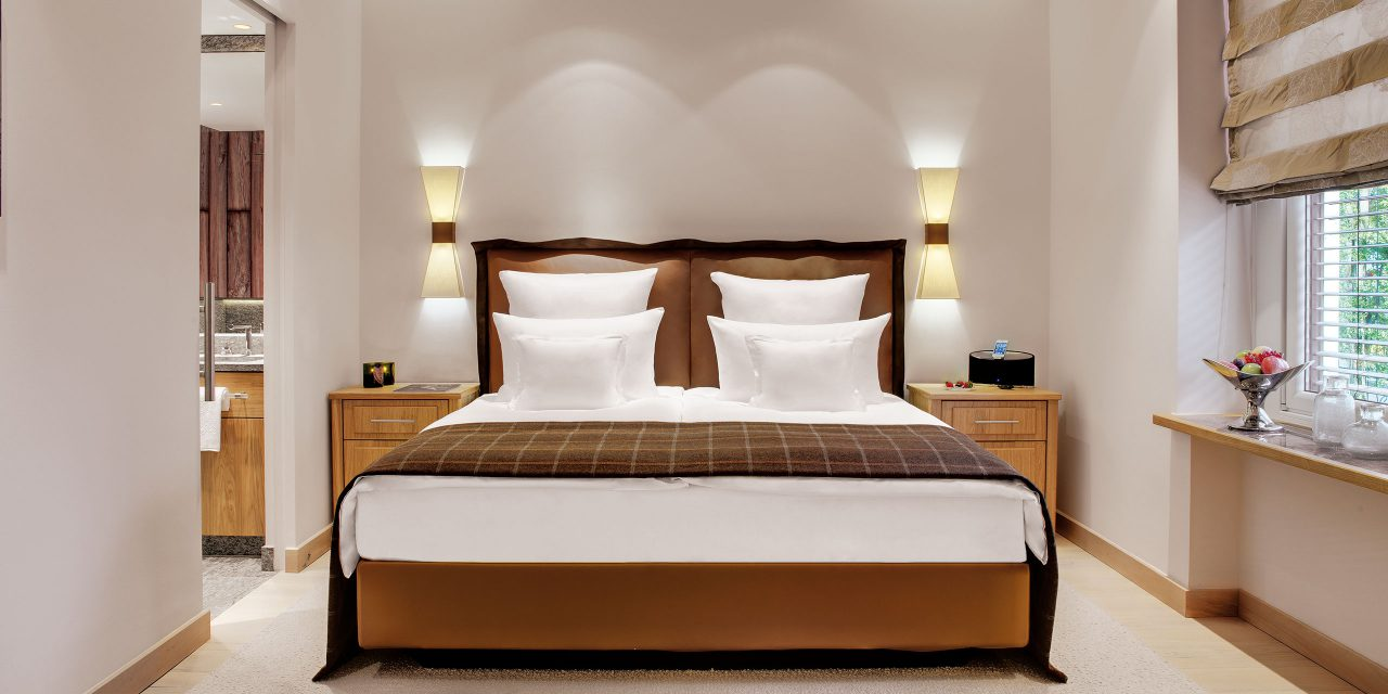 Bright and modern room with atmospheric wall lamps to the right and left of the large bed and view of the a tree summit in Hotel Excelsior.