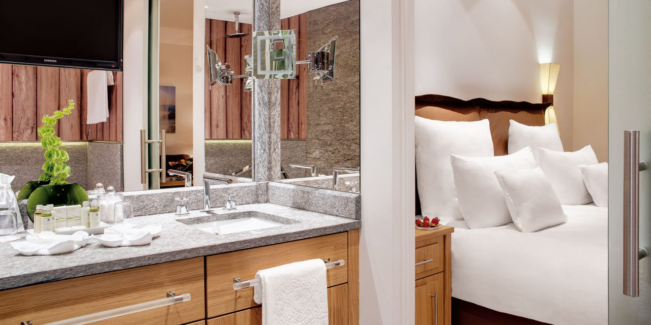 Hotel room in the Excelsior in downtown Munich with large bed, atmospheric lighting and bathroom with natural stone and care products.
