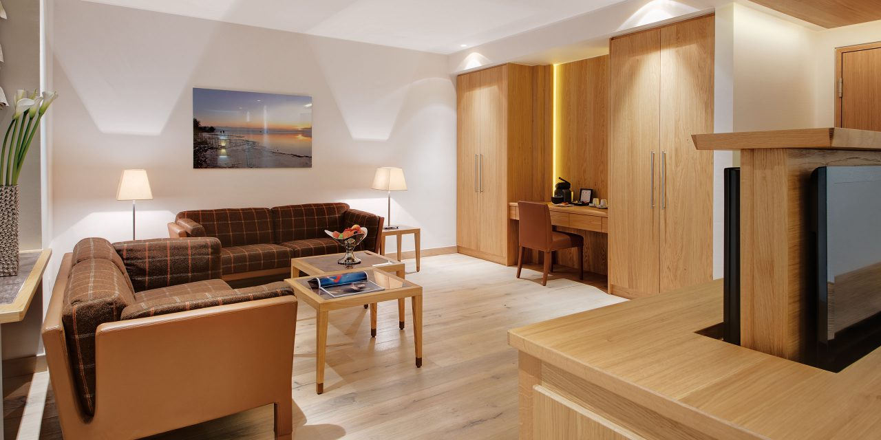 Modern hotel suite in the centre of Munich with two sofas, desk corner and lateral view of a TV wall that can be raised on both sides.