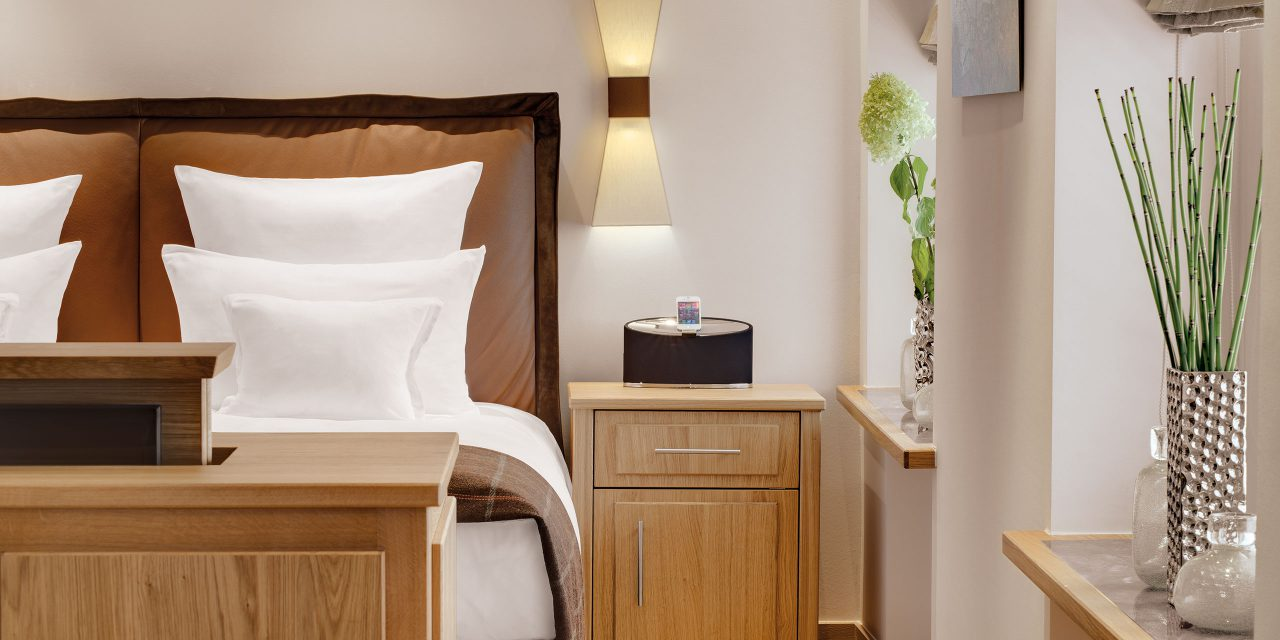 Room 36 of Hotel Excelsior with comfortable and luxurious double bed, bedside cabinet and stylish vases on the windowsill.