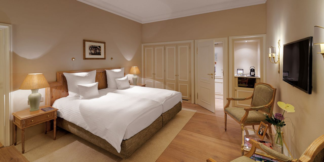 Room 37 in Hotel Excelsior with large double bed, flat screen TV, seating, comfortable lighting and beige wall colour.