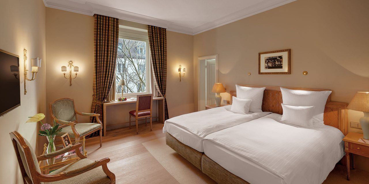 Bavarian furnished hotel room in Munich with large bed, wooden chairs, tables and checked curtains.
