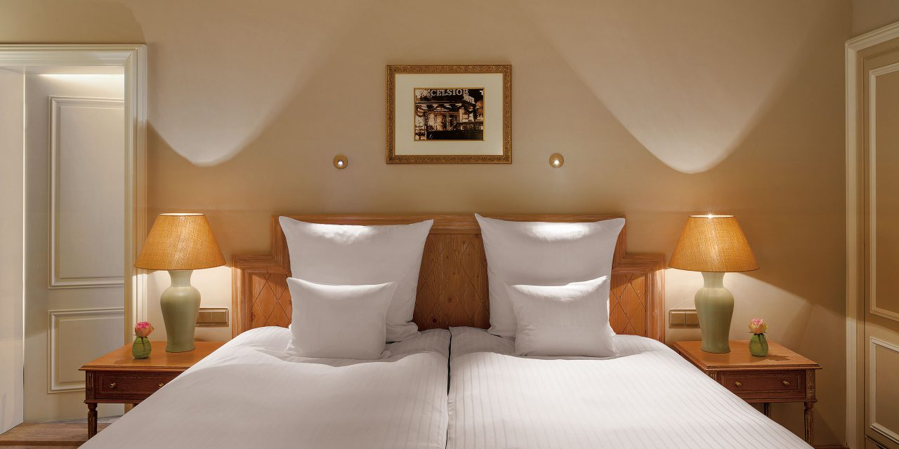 Double bed over which hangs a picture of the hotel Excelsior with two bedside tables with table lamps and half-opened door to the bathroom.