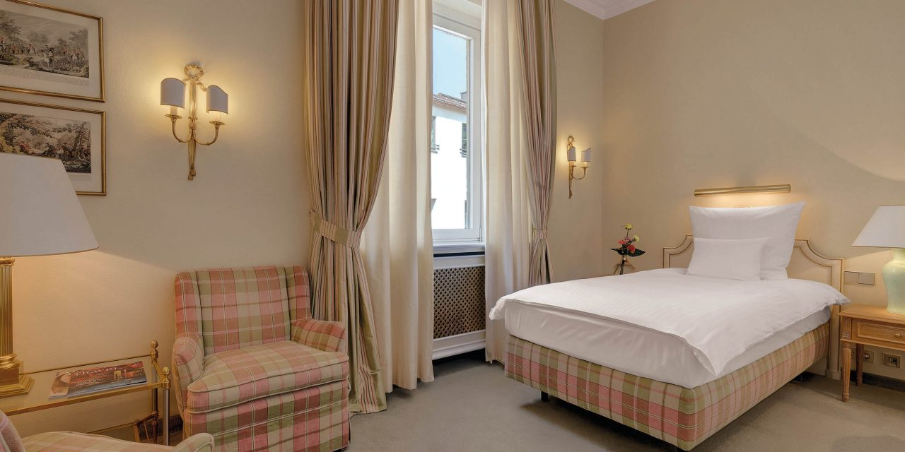 Single room classic in the hotel Excelsior with pink-beige chequered armchair, table with lamp, comfortable bed and bright window with curtains.