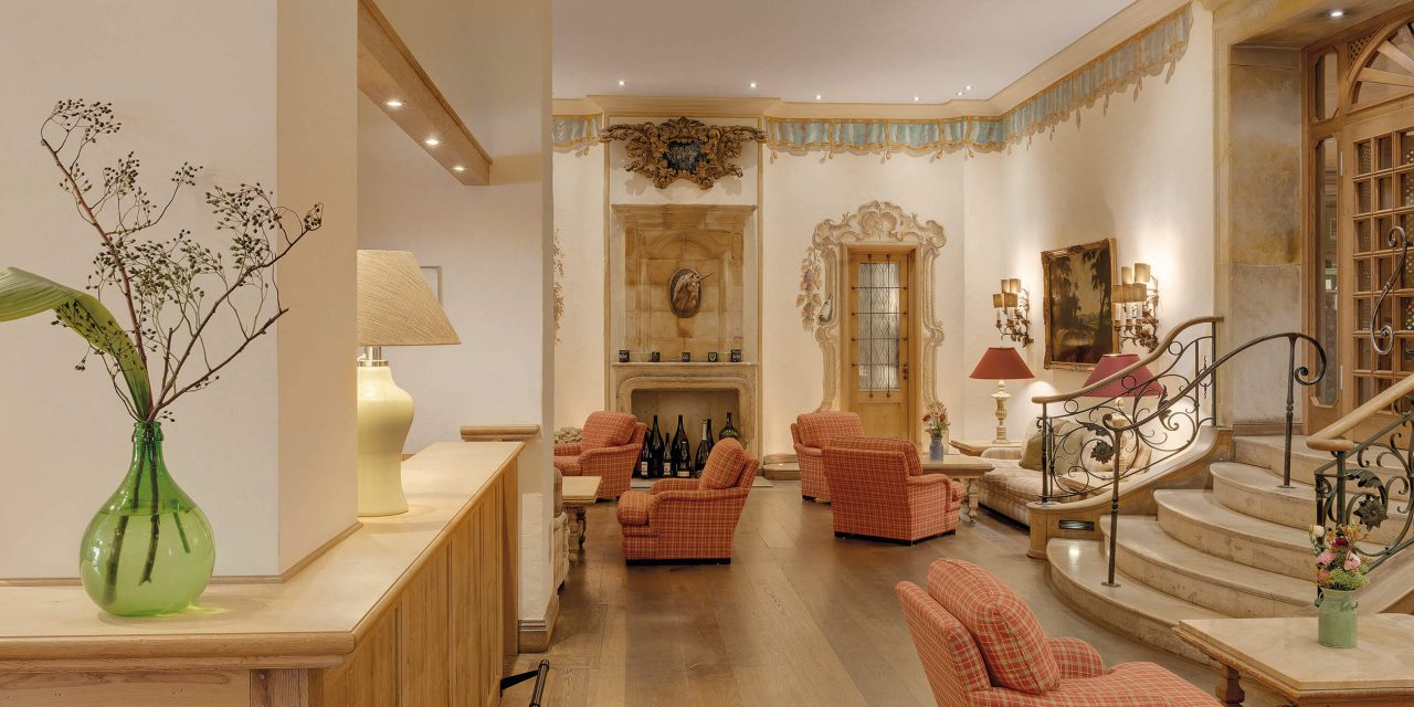 Cosy and bright lobby of the Hotel Excelsior in Munich city centre with comfortable armchairs, atmospheric table lamps and stucco decorations on the walls.
