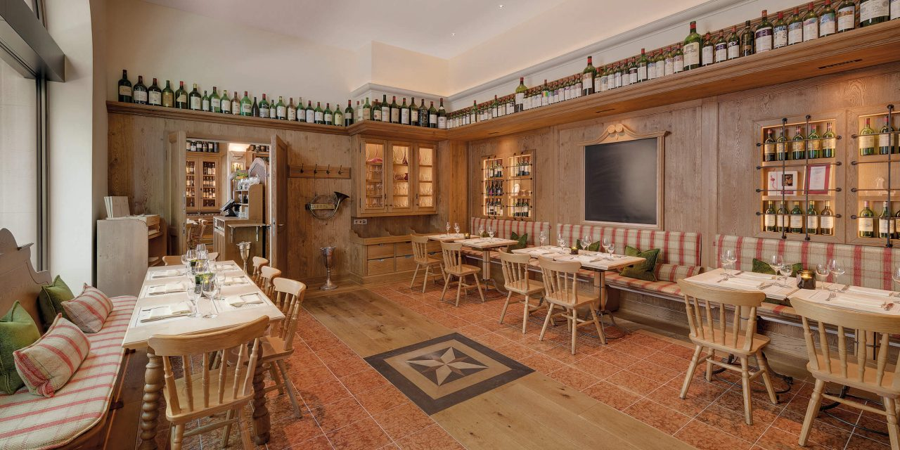 Wine bar in Munich with wooden walls, wooden floor with pattern in combination with tiles, covered tables and comfortably upholstered benches as well as a continuous shelf under the ceiling with wine bottles.